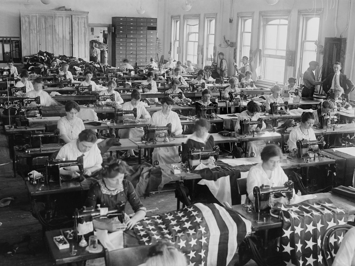 Black and white historic photo of rows of women at tables sewing American flags.