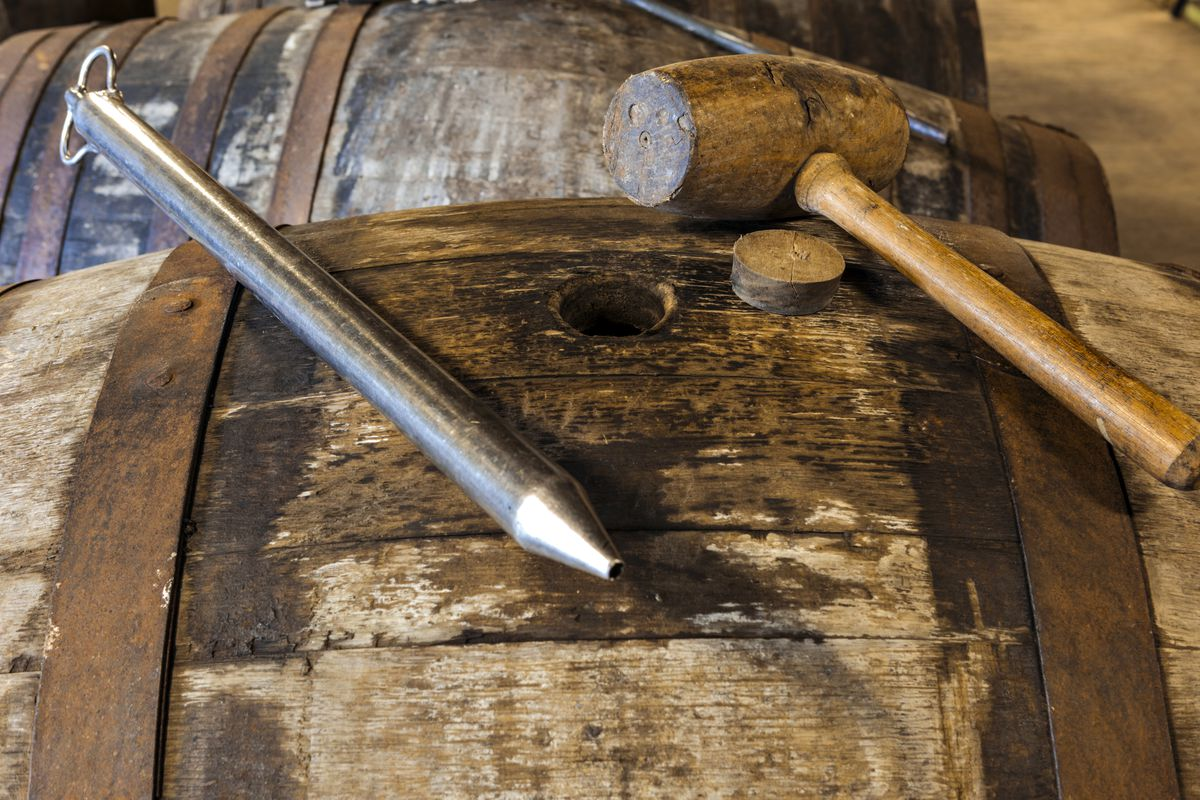 A charred barrel lies on its side with its round opening facing up. Resting on the barrel is a long metal pipette, a cork, and a wooden mallet.