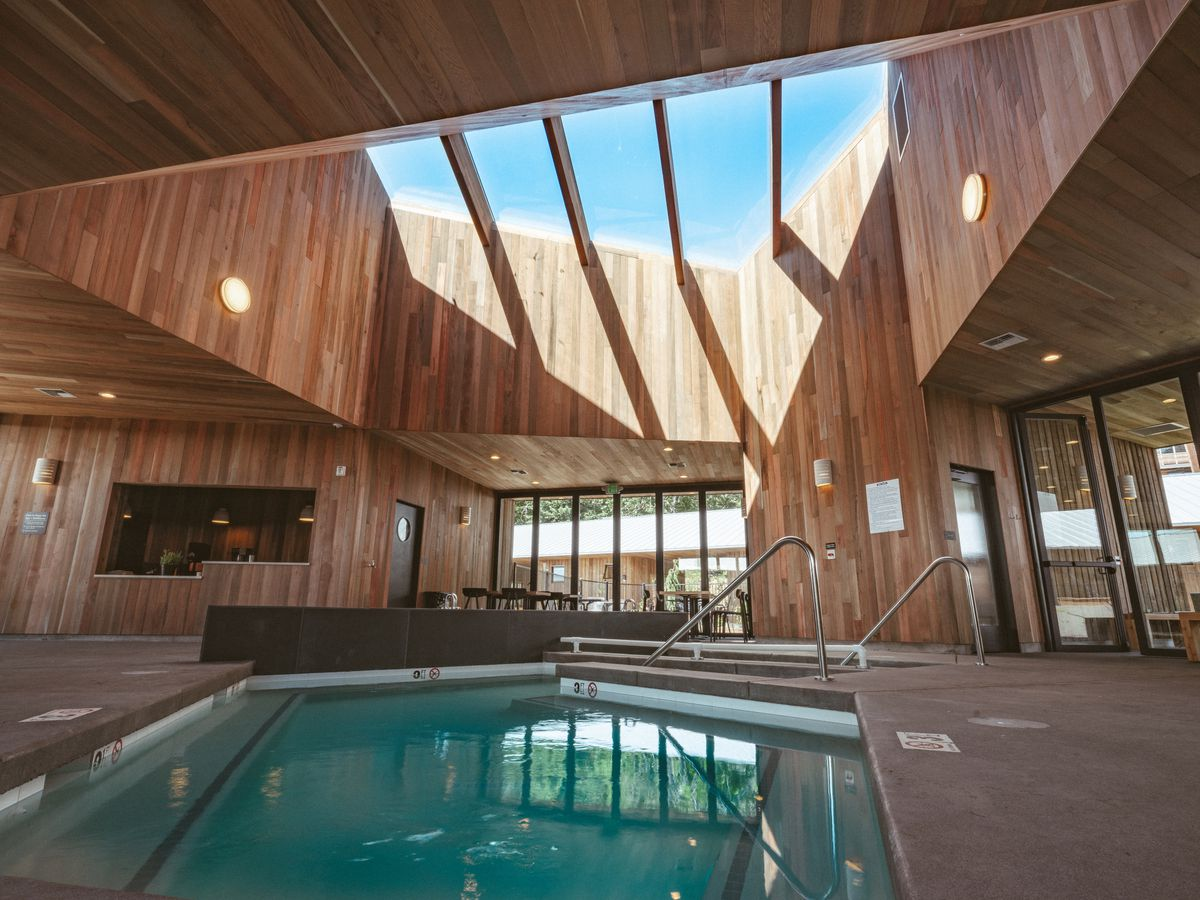Indoor pool surrounded by wooden walls and large skylight above.