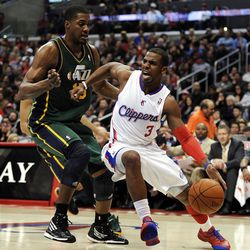 LOS ANGELES, CA - MARCH 31:  Chris Paul #3 of the Los Angeles Clippers keeps his dribble from Derrick Favors #15 of the Utah Jazz at Staples Center on March 31, 2012 in Los Angeles, California.  NOTE TO USER: User expressly acknowledges and agrees that, by downloading and or using this photograph, User is consenting to the terms and conditions of the Getty Images License Agreement.  (Photo by Harry How/Getty Images)