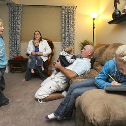 8-year-old Mykenzie Burton, right, draws as 6-year-old Porter talks to mom, Mary, with 3-year-old Logan wrapped in her jacket and Kelly holding 2-month-old Raiger in their home Sept. 25.