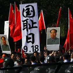 """Anti-Japan protesters hold portraits of the late Communist leader Mao Zedong, Chinese national flags, and a poster that reads: """"Sept. 18, National Humiliation Day,"""" while marching on a street outside the Japanese Embassy in Beijing Tuesday, Sept. 18, 2012. The 81st anniversary of a Japanese invasion brought a fresh wave of anti-Japan demonstrations in China on Tuesday, with thousands of protesters venting anger over the colonial past and a current dispute involving contested islands in the East China Sea."""