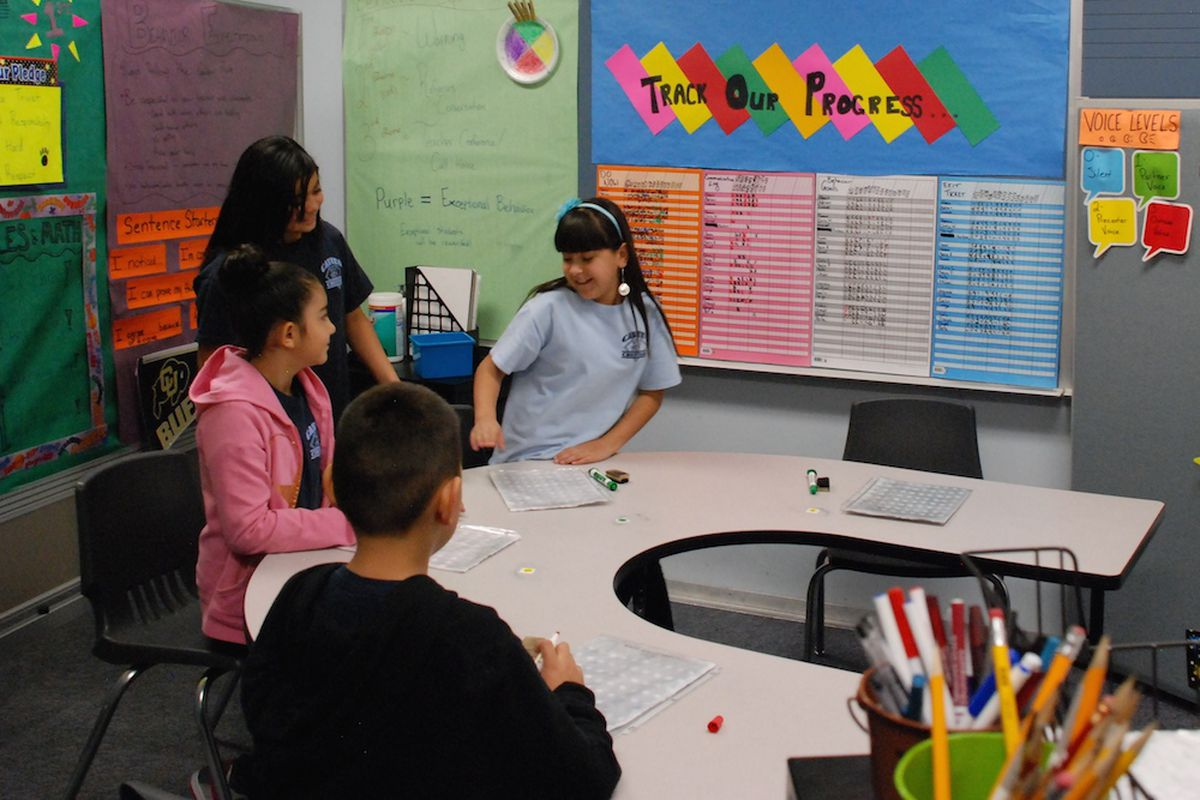 Students work on their math skills at Castro Elementary School in Denver. Behind them is a progress chart. Several schools, like Crawford Elementary in Aurora, track student progress against its Unified Improvement Plan.