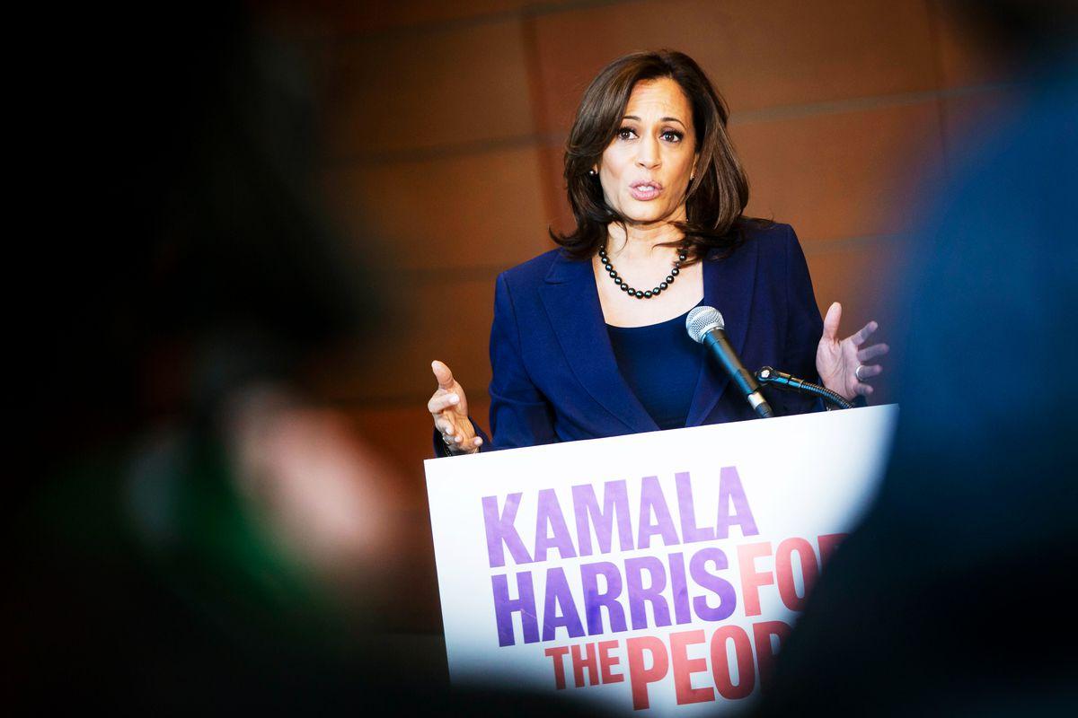 "Senator Kamala Harris speaking from behind a podium with the sign ""Kamala Harris for the people."""