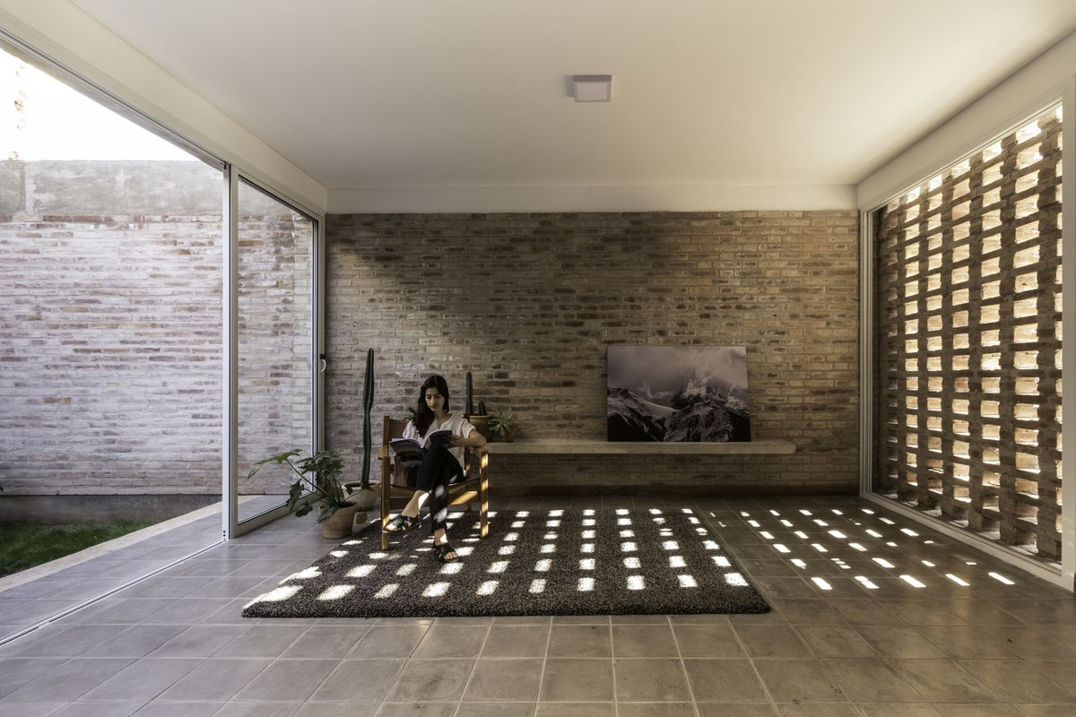 Woman sitting in interior courtyard with brick wall and screen.