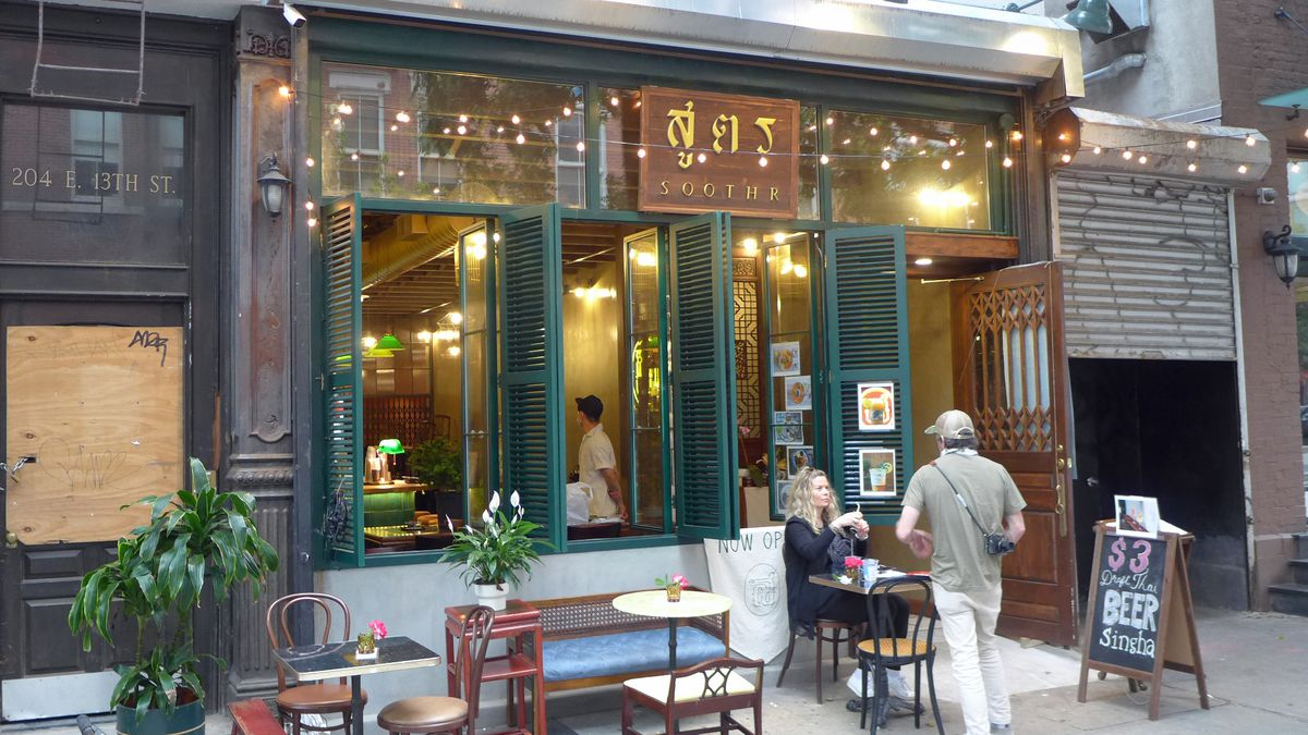 A restaurant facade open at the front with a couple of tables on the sidewalk.