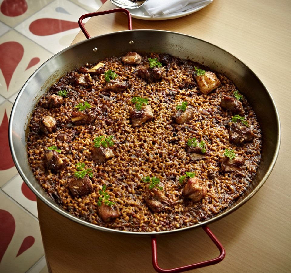 A skillet filled with sausage-flecked paella