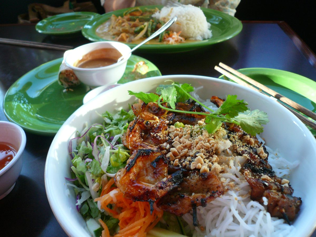 A close-up shot of a bowl of grilled pork, cilantro and carrots on top of vermicelli noodles