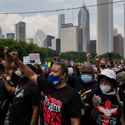 Community activists raise their fists during a march that commemorates Juneteenth in downtown Chicago on June 19, 2020.