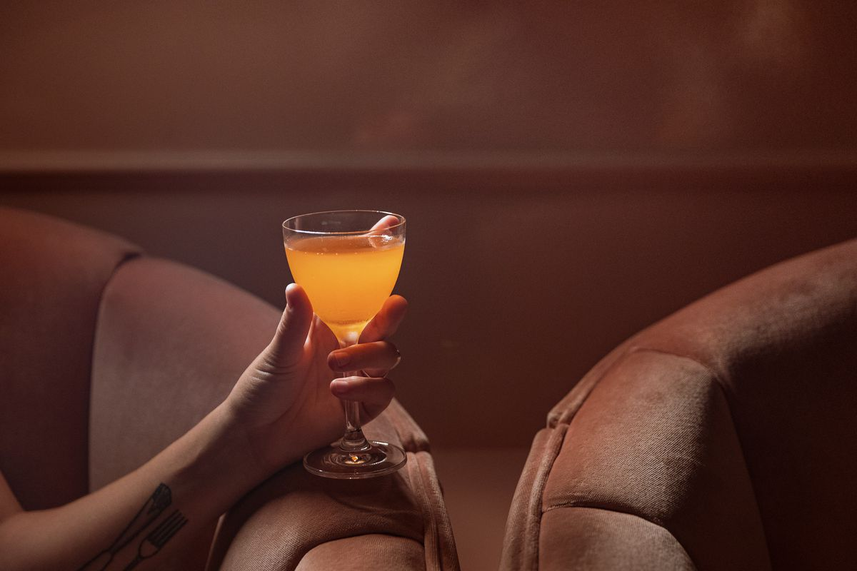 a coup filled with yellow liquid held in a woman's hand on a pink couch