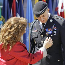 Denise Meehan looks at the Distinguished Service Cross awarded to Sgt. Felipe Pereira on Thursday, April 12, 2012, at Fort Campbell, Ky. Pereira suffered shrapnel wounds to his spleen, lung and liver when his unit was attacked in November 2010 in Kandahar province, but he refused medical treatment and helped to evacuate two other wounded soldiers. Meehan's son, Pfc. Andrew Meari, was killed in the attack. AP Photo/Mark Humphrey)