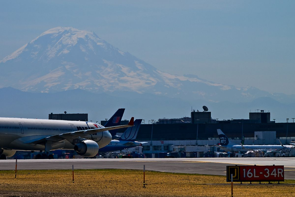 Seattle-Tacoma International Airport with an airplane on a runway in the foreground and Mt. Rainier in the background.