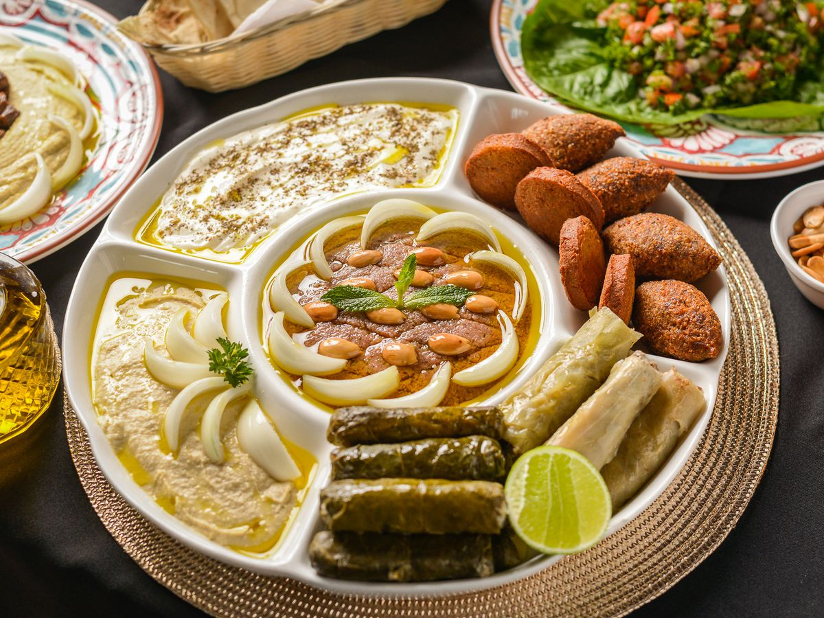 A round segmented dish with dips, falafel, and stuffed grape leaves in the various trays, with other dishes blurred in the background