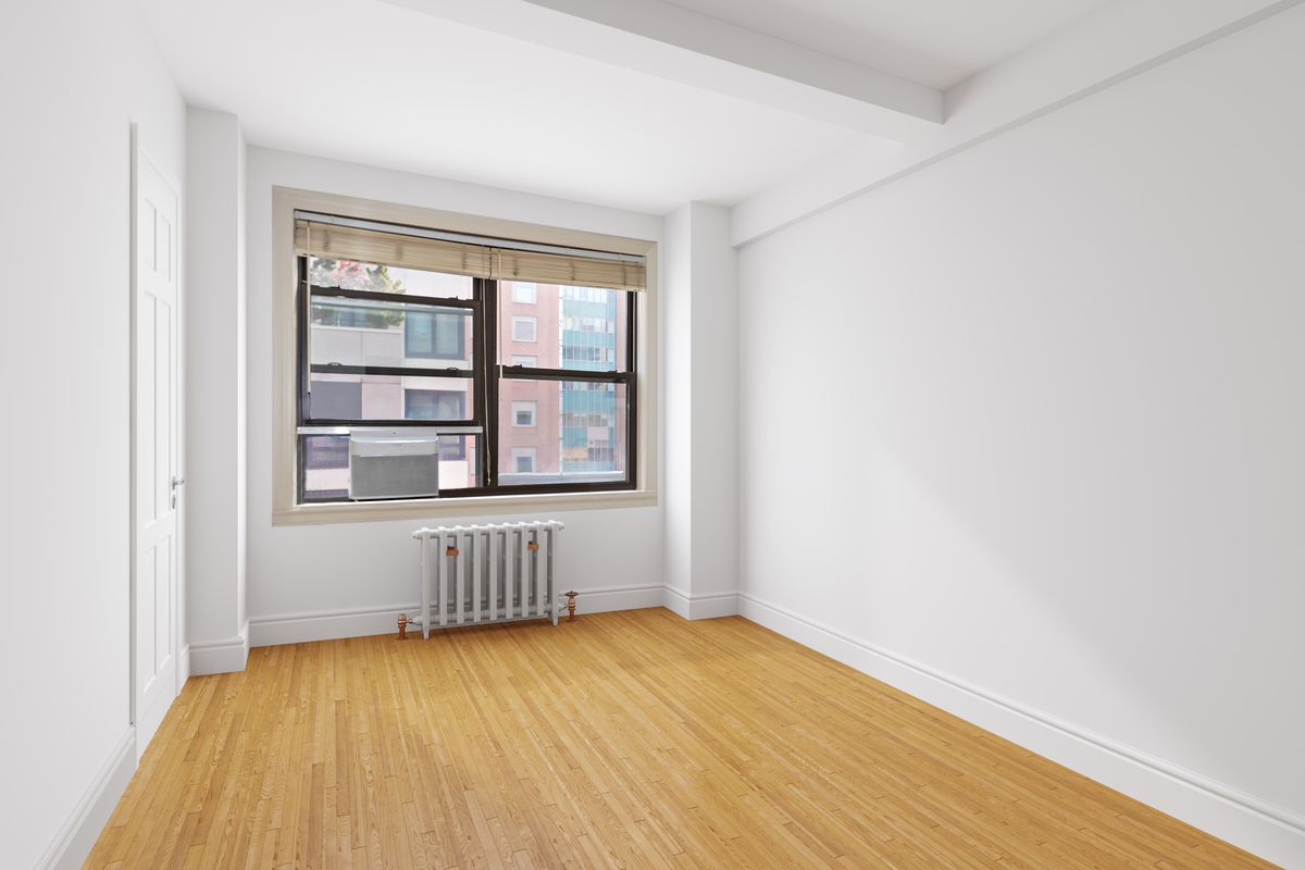 A living area with a window, beamed ceilings, hardwood floors, and white walls.
