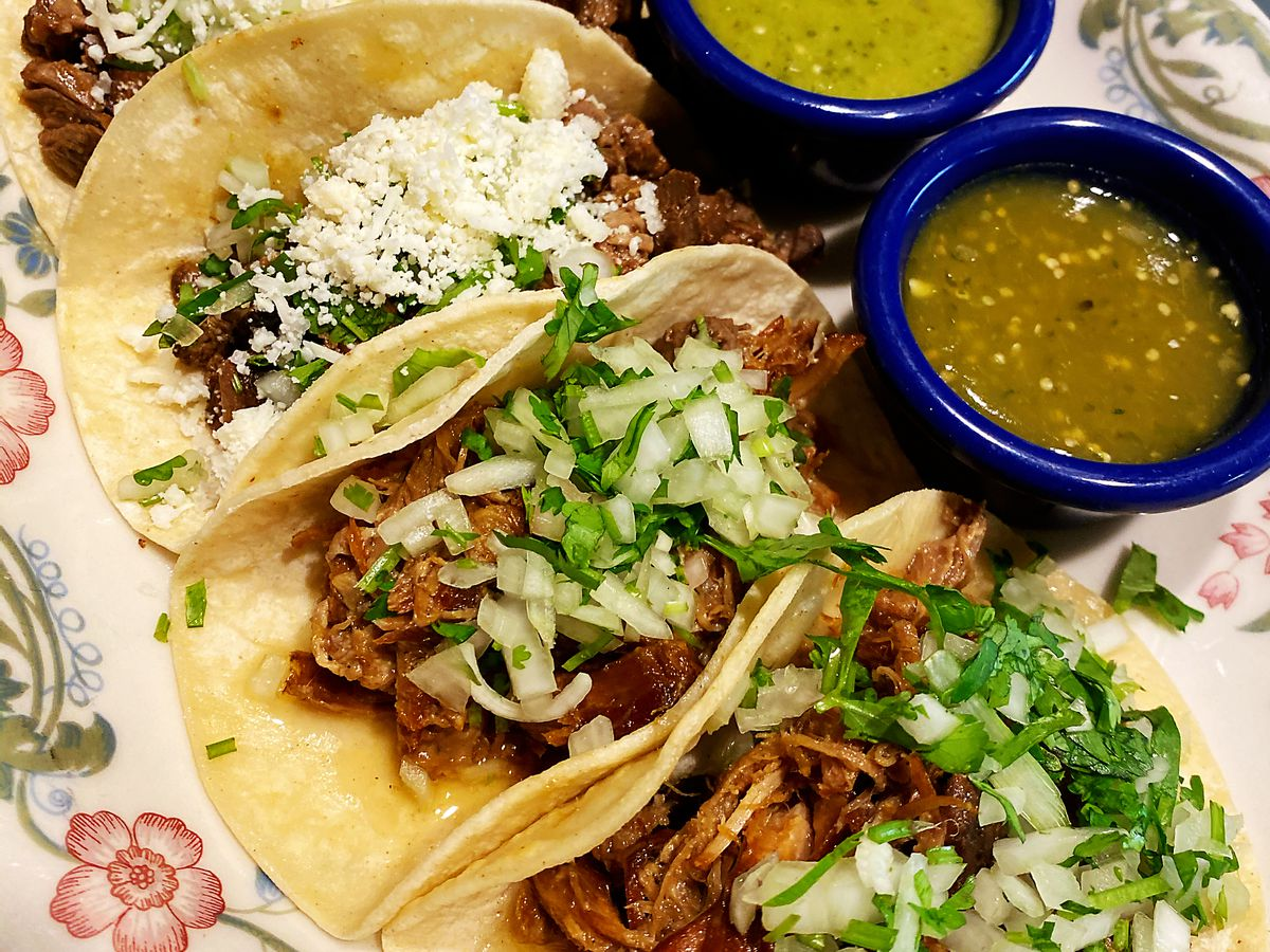 Plate of three tacos and salsa.