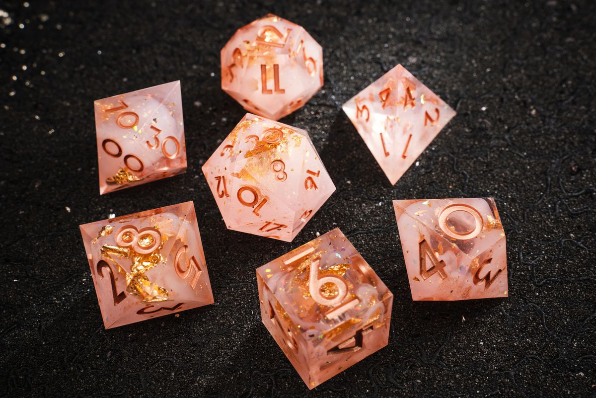 Gold fleck emerges from inside peach-colored dice.