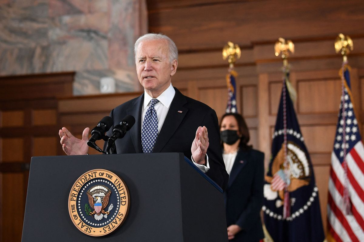 Biden, in a dark suit and blue tie, speaks at a podium bearing the seal of the US. Vice President Kamala Harris stands behind him, in a black suit and white blouse.