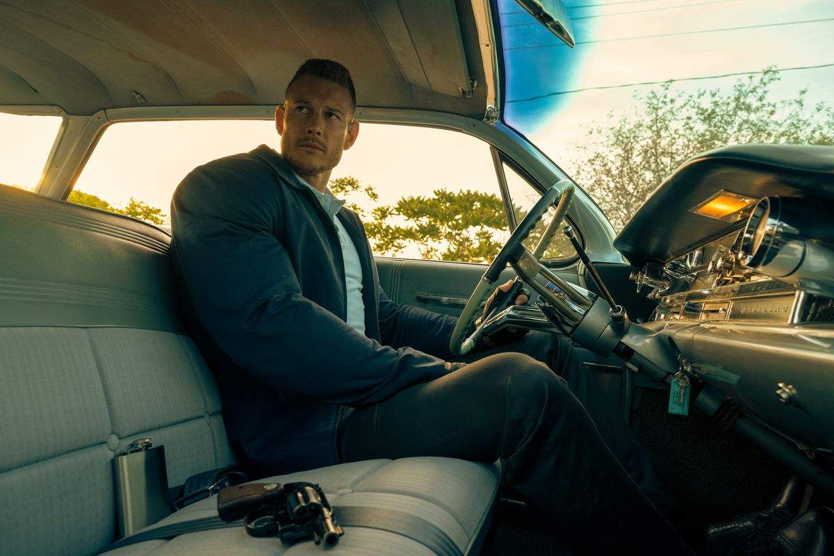 luther sitting in a car, looking more or less the same tbh, we're not here for him