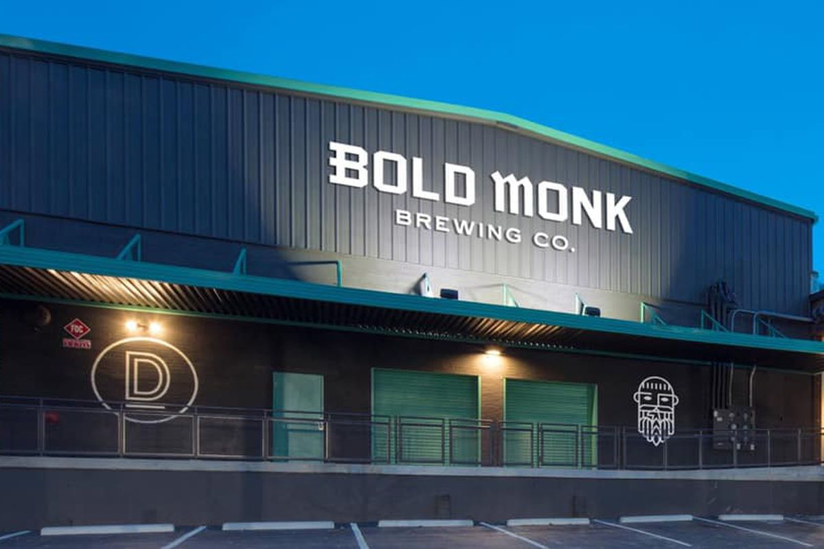 The exterior of Bold Monk Brewpub lit up at night