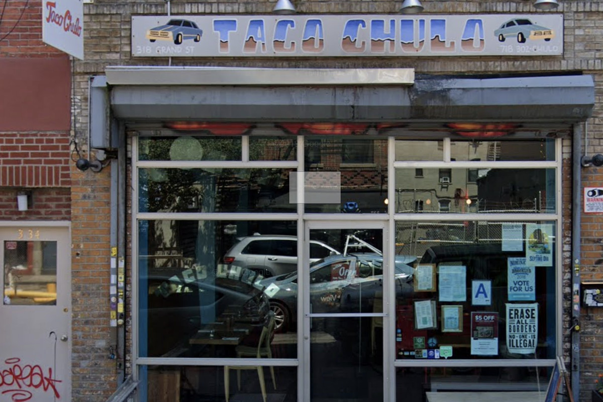 The exterior of a restaurant with a glass door and a wooden sign hanging in the front that says Taco Chulo