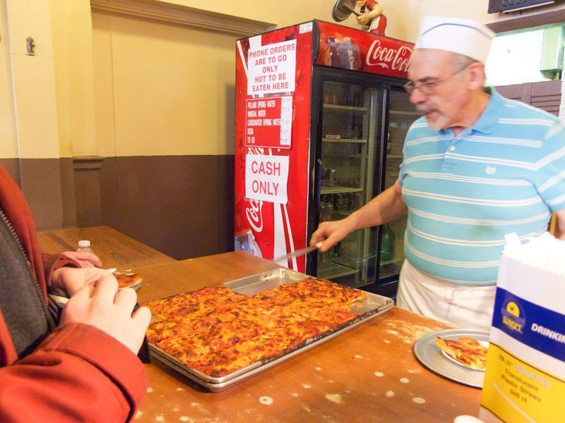 A man in a blue shirt with white stripes and a white hat and apron serves Sicilian-style pizza at a counter. A Coca-Cola fridge is visible in the background.