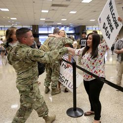 First Lt. Taylor Duke holds his daughter Leslee Duke and walks towards his wife Amanda Duke at the Salt Lake International Airport in Salt Lake City on Tuesday, Aug. 27, 2019, as he and other members of the Utah National Guard's 4th Infantry Division Main Command Post Operational Detachment return home after serving in Afghanistan for 10 months in support of Operation Freedom's Sentinel.