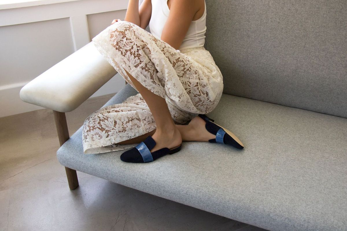 A women curled up in a chair in backless loafers.