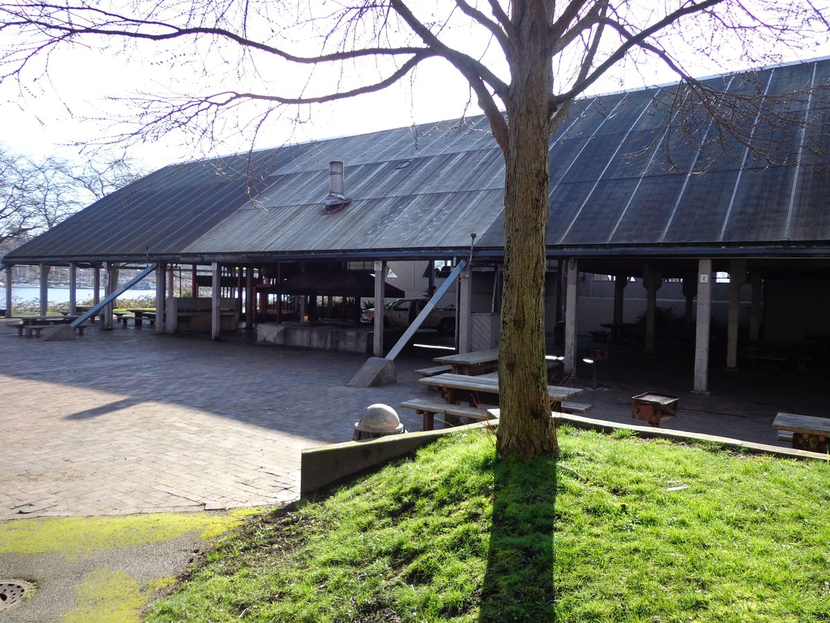 Two connected picnic shelters with a steep roof and a concrete patio in front.
