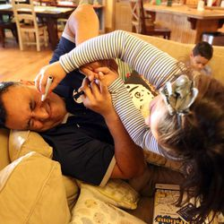 Kalani Sitake tries to avoid his daugher Sadie's attempt to draw on him at home in Provo on Friday, March 11, 2016.