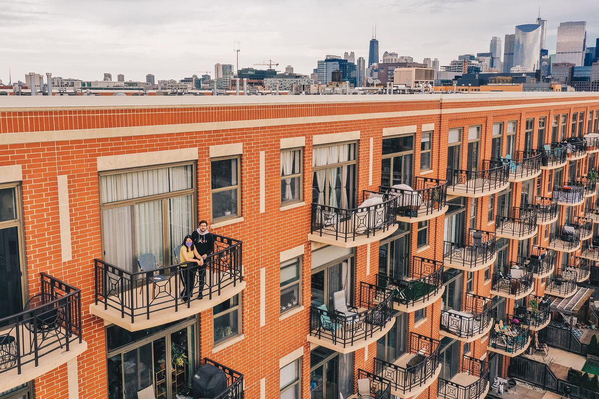 Helena Kim and her fiance, David Romano, on the balcony of their West Loop apartment.