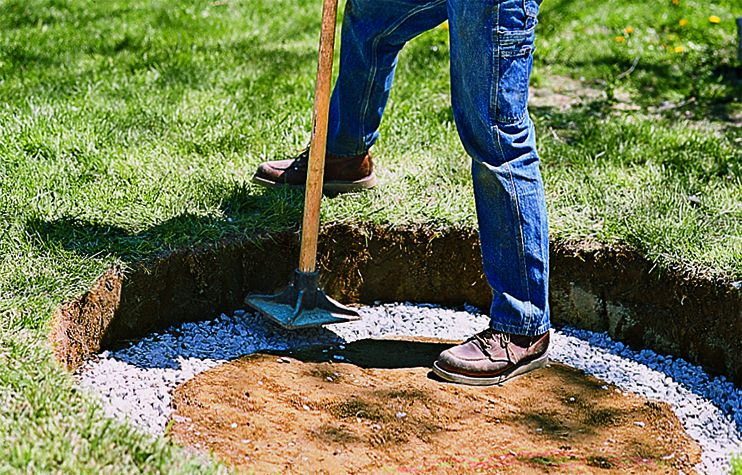 Man Tamps Down Gravel In Fire Pit With Hand Tamper