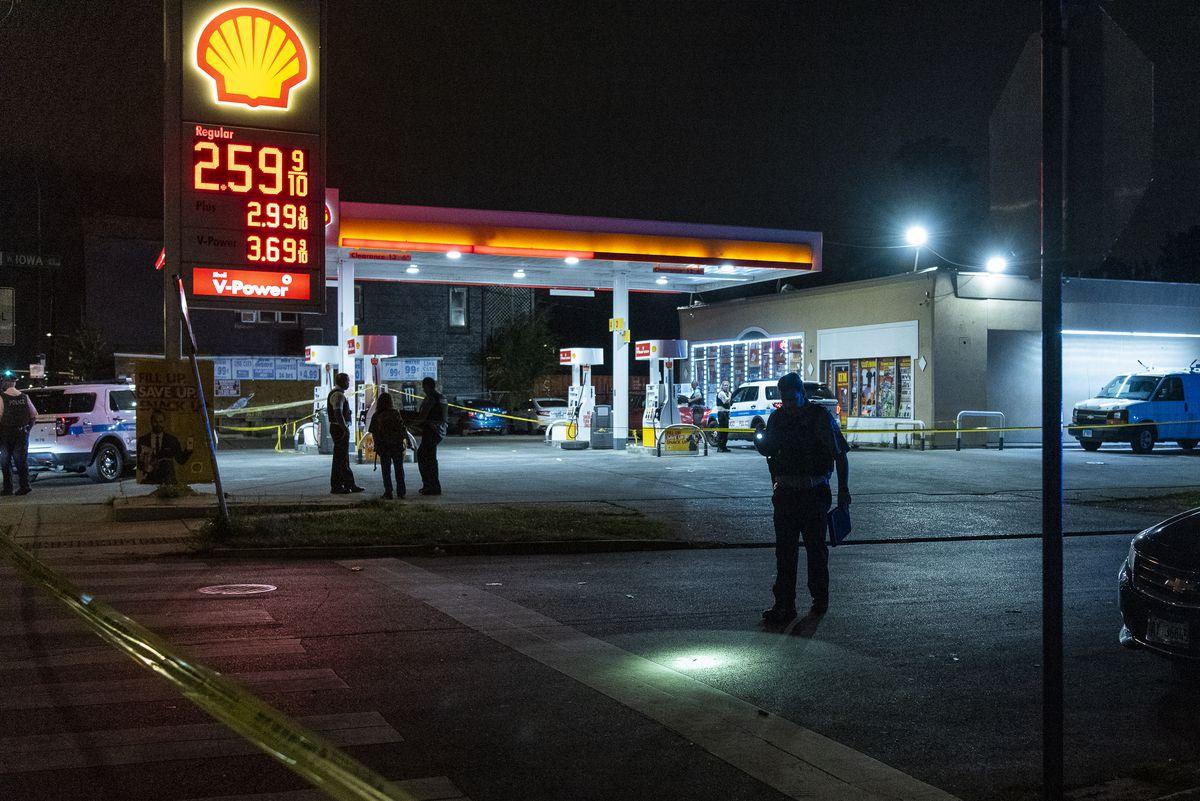 Chicago police at the scene of a shooting Friday night at a Shell gas station in the 900 block of North Pulaski Road that left one man dead and another wounded.