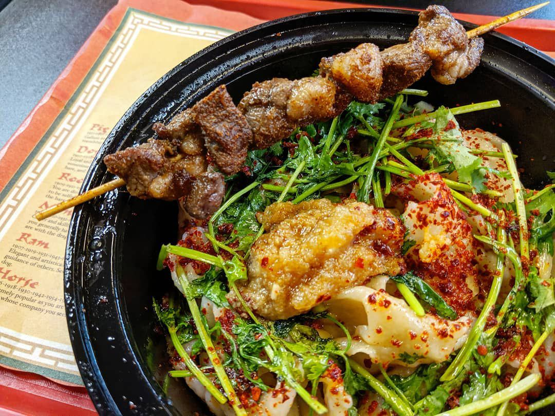 A black plastic bowl of thick hand-pulled noodles, heavily dusted with chile powder and topped with greens and a generous dollop of garlic. A wooden skewer of lamb pieces sits across the rim of the bowl, which is on a Chinese Zodiac placemat on a red tray