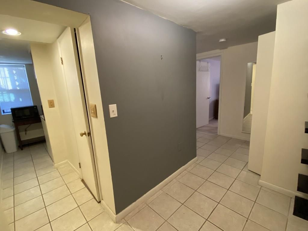 A small foyer with tile flooring and doors off it.