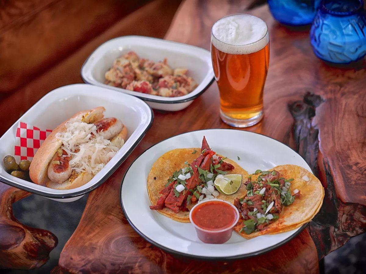 A photo of a plate with two corn-shell tacos on it, another plate with a bratwurst topped with onions and a glass of beer that have been placed on a table at Ecclesia Market