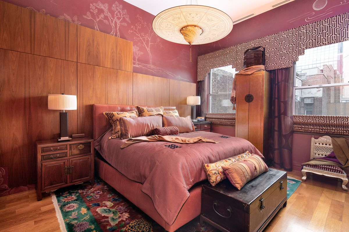 A bedroom with a red wallpaper, hardwood floors, a large bed, and wooden furniture.