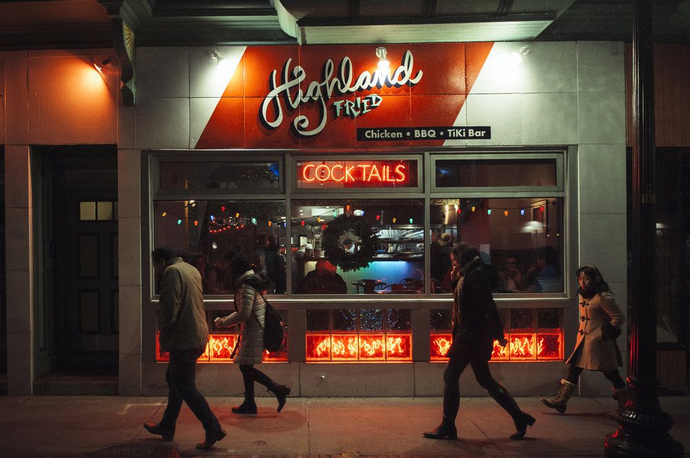 """The exterior of a restaurant with red and light blue paint and neon signage reading """"cocktails."""" Cursive letters spell out the restaurant's name, Highland Fried."""