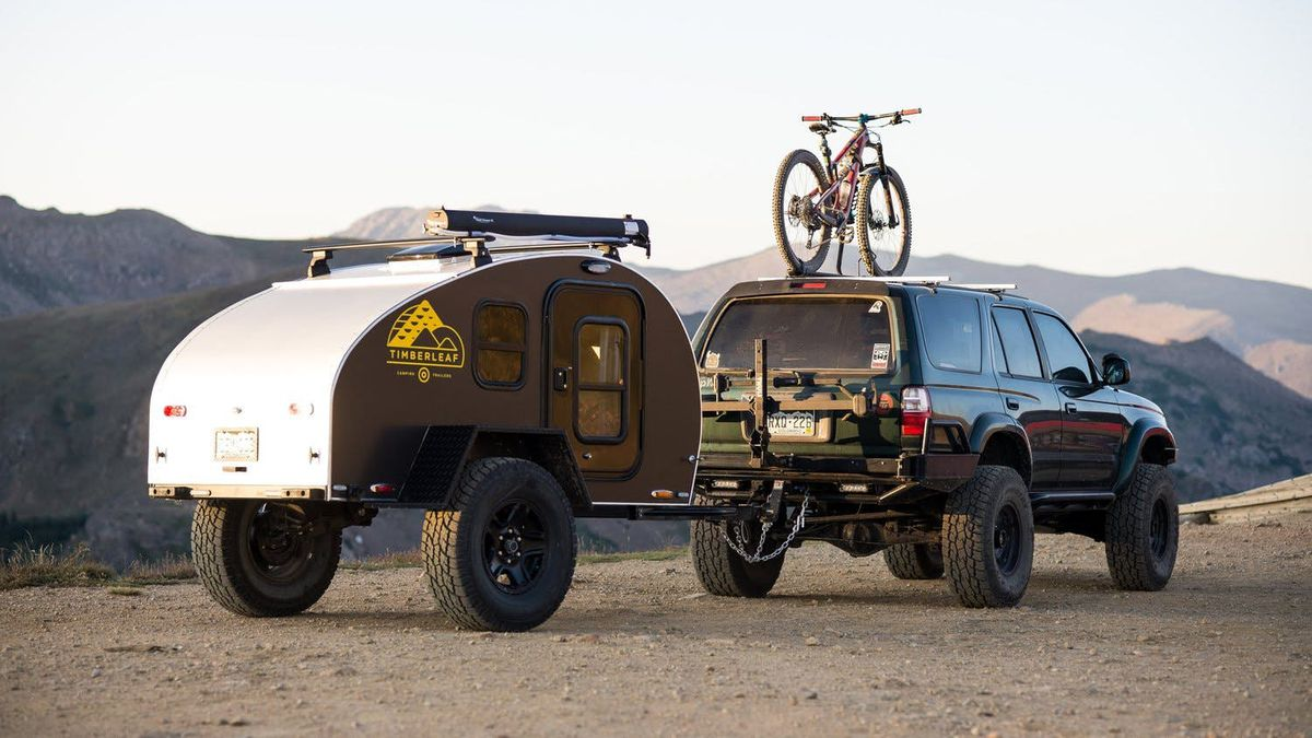 A small trailer is attached to a jeep. The trailer is brown. The jeep is green and has a bicycle on top of it.