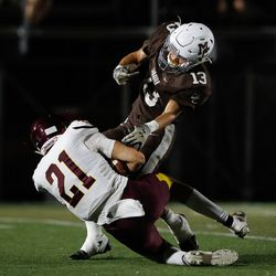 Montini's Nate Muersch (21) is tackled by Mount Carmel's Martin O'Brien (13).