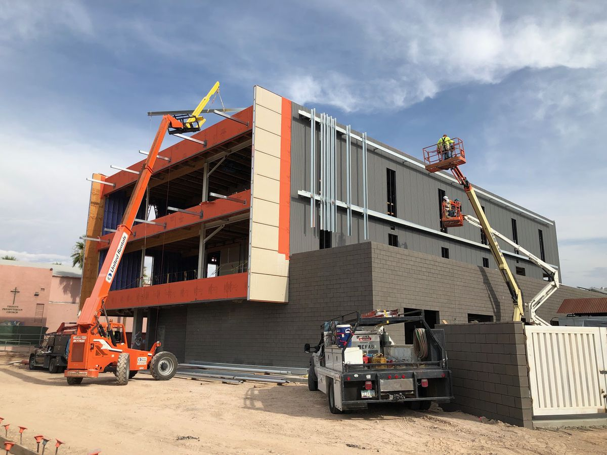 A two-story orange and gray building under construction with several large lifts holding construction workers.
