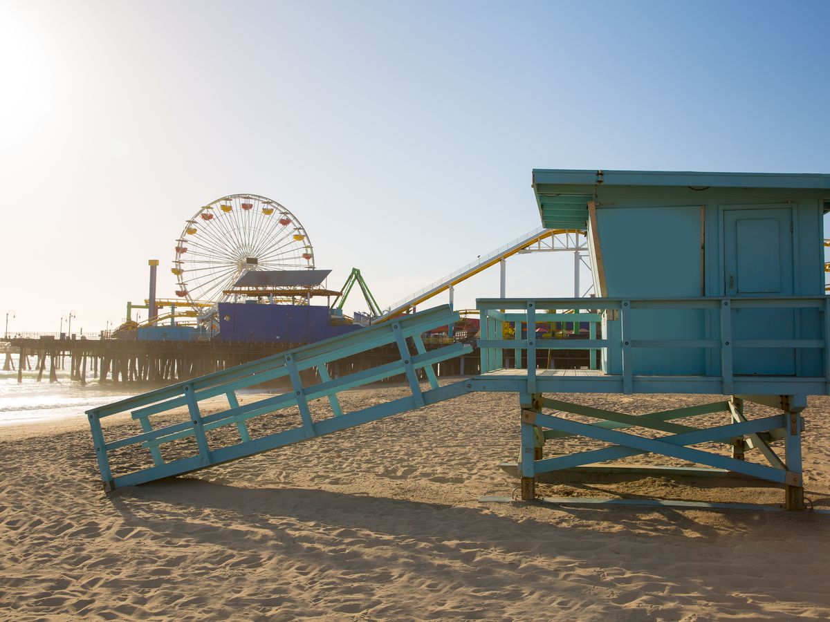 A sandy beach with a blue lifeguard tower. There is a ferris wheel in the distance near a pier.