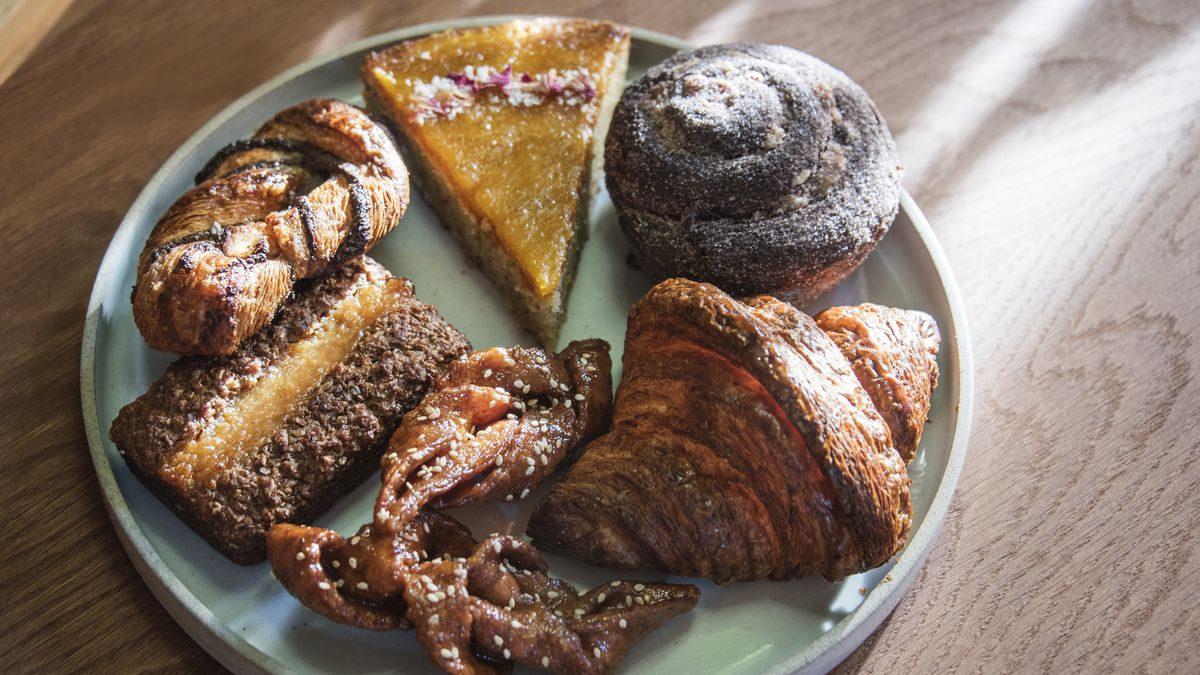 Six assorted baked pastries and confections sit on a light blue plate