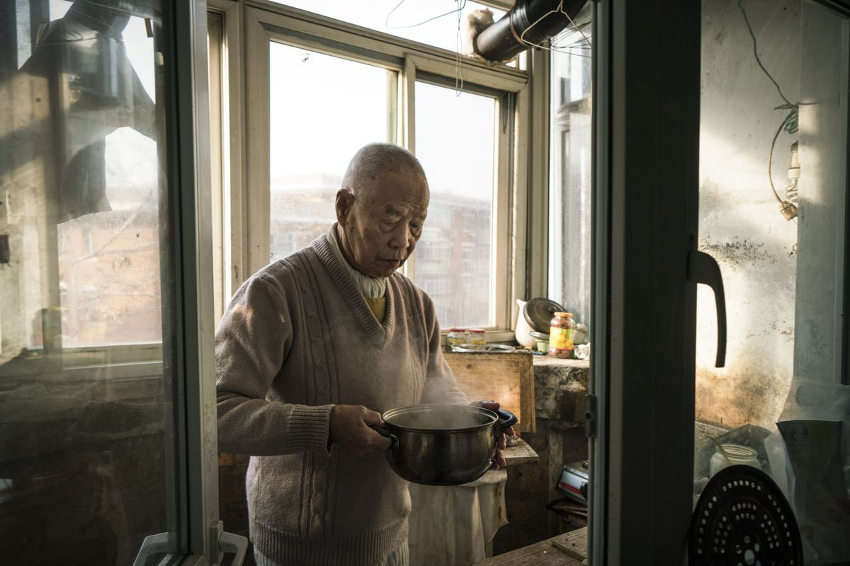 January 19: Han Zicheng, 85, holds his breakfast, a pot of boiled soy milk, in his kitchen in Tianjin, China. He was one of millions of Chinese seniors growing old alone. So he put himself up for adoption.Read More. (Yan Cong for The Washington Post