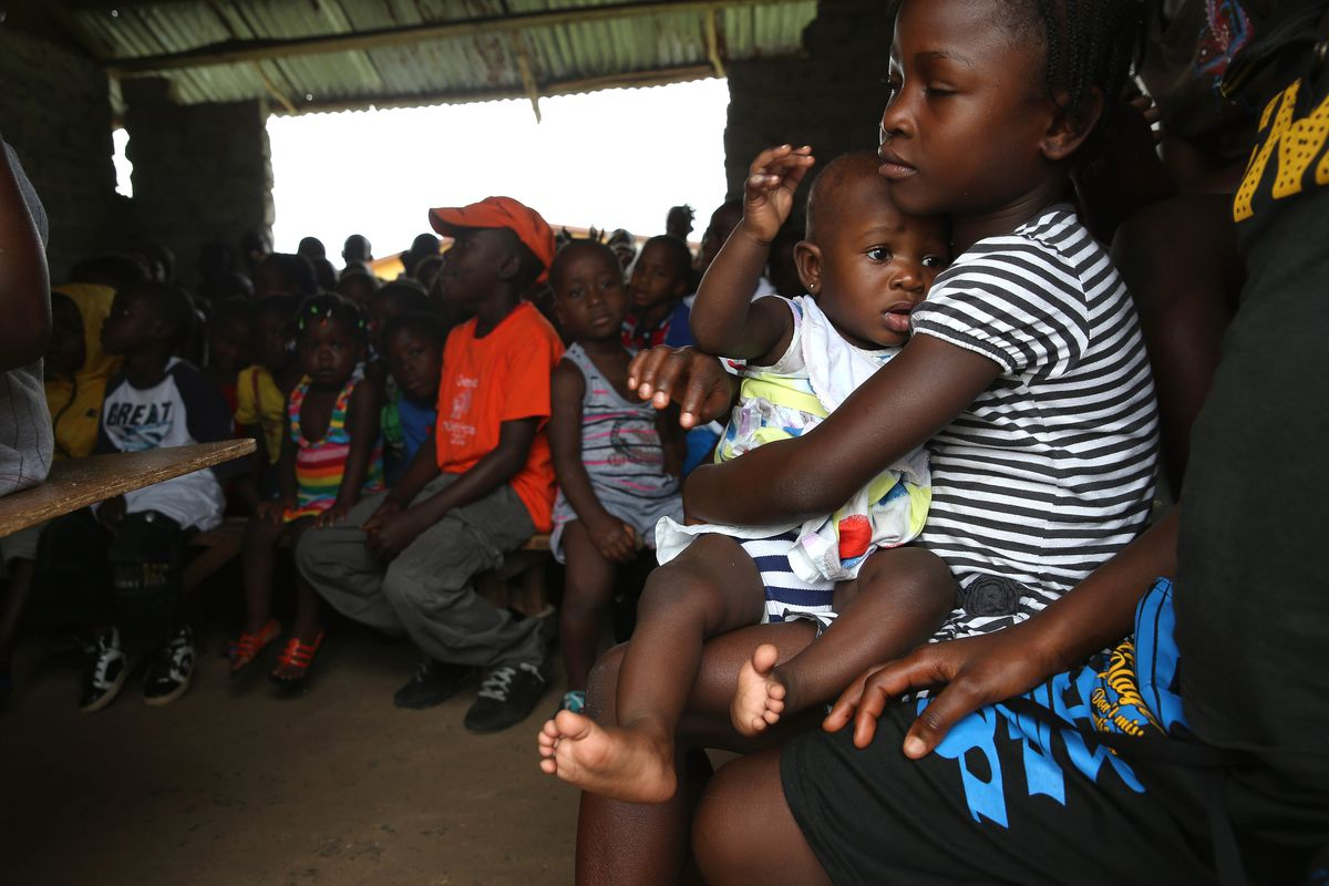 Children sit during a Sunday church service in Dolo Town, Liberia.