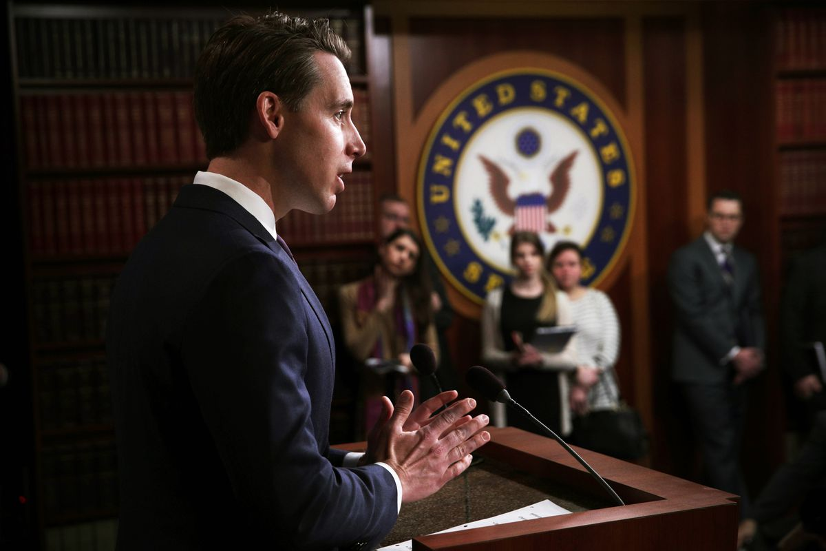 Senator Josh Hawley speaking from a podium in the US Capitol. Listeners stand beside a large seal of the United States Senate.