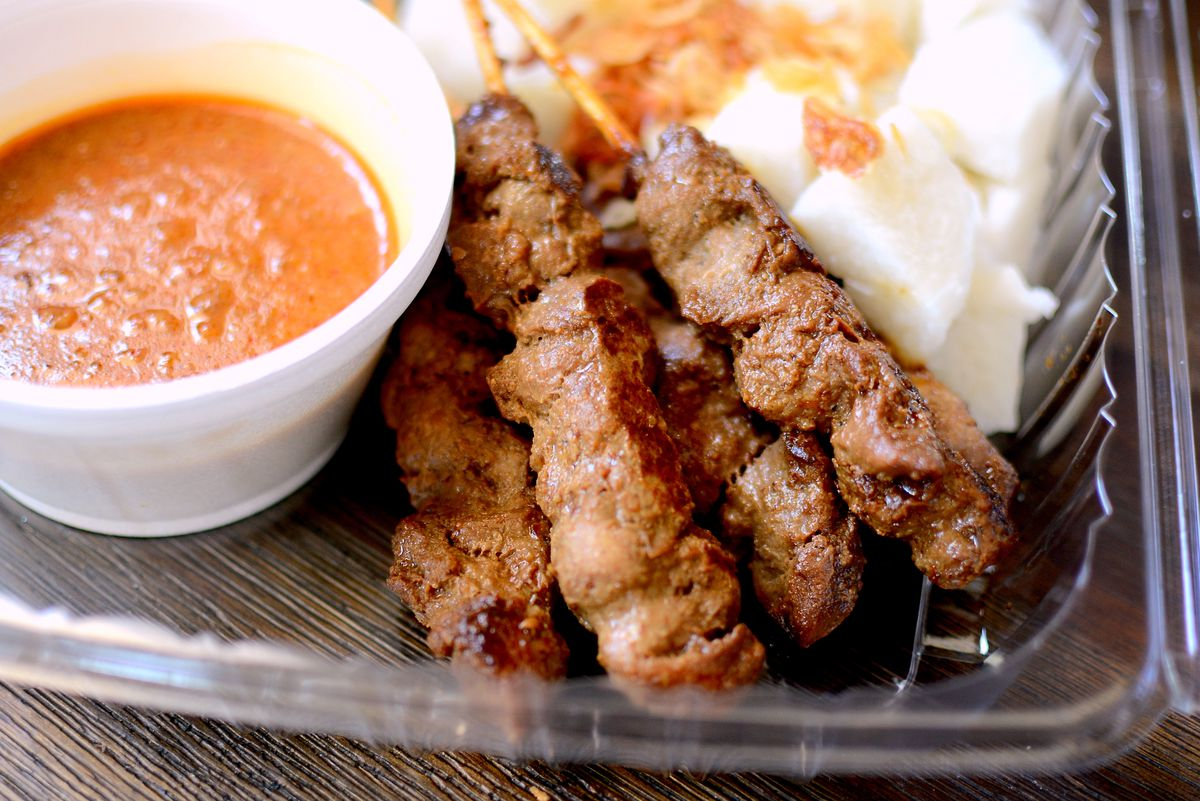 A container with grilled pork on a stick with compressed rice and peanut sauce.