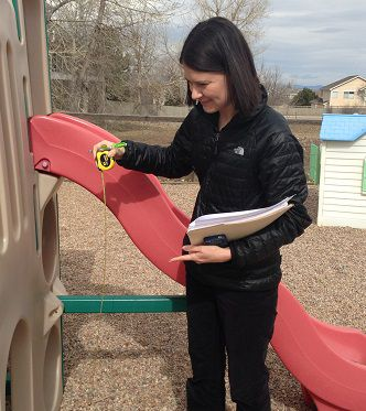 Qualister rater Terri Stowell measures the slide height as part of her assessment of the playground.
