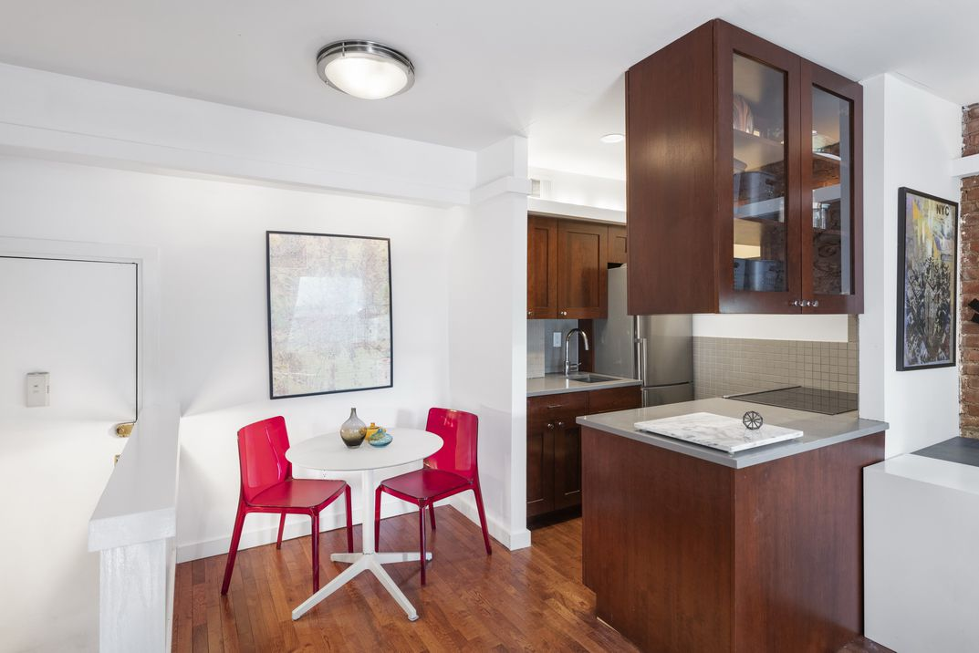 A dining area with a small, white round table, two bright red chairs, and the kitchen on the right side.