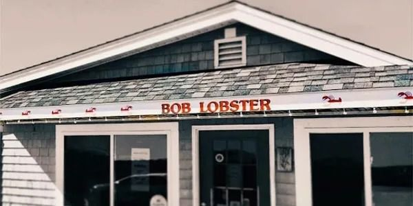 """gray-shingled exterior of a restaurant with a few small red lobsters painted above the windows and """"Bob Lobster"""" in red"""