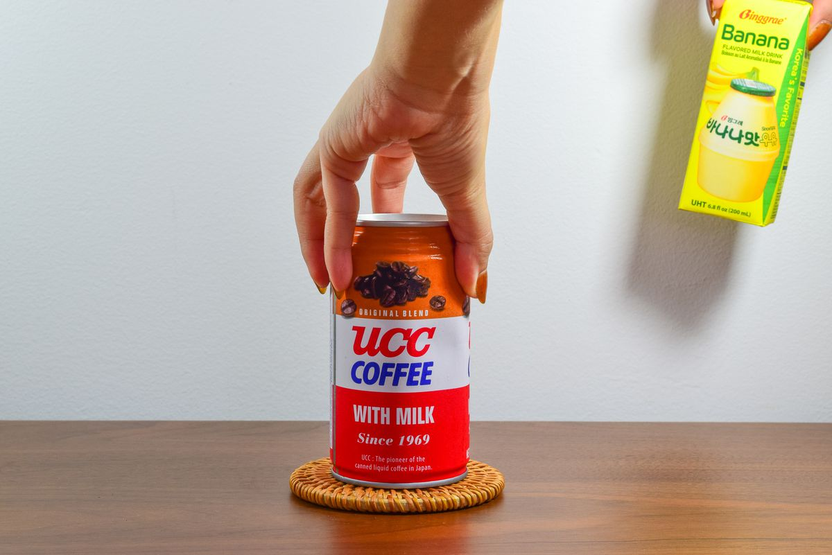 Hand reaches over a can of UCC Coffee that's sitting on a coaster on a wooden tabletop.